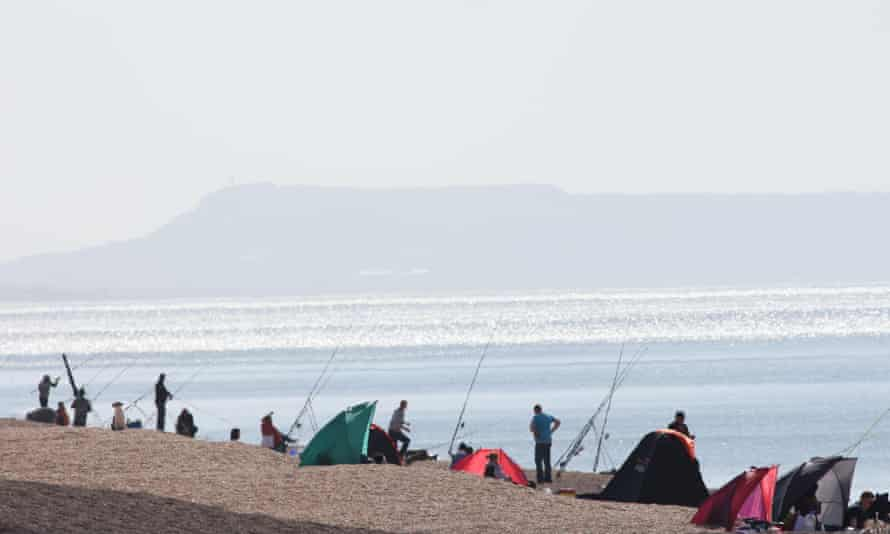 Anglers in a heat haze on a scorching day on Chesil Beach, with Portland Bill in the background.