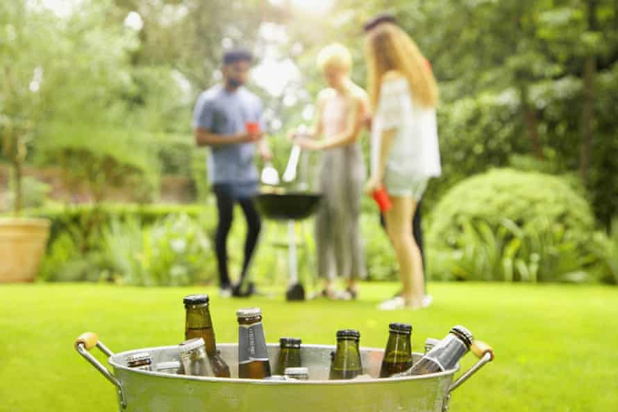 Beer bottles in bucket while friends enjoying barbecue party in background at yardBeer bottles in bucket while friends enjoying barbecue party in background at yard