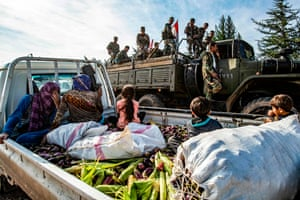 Soldiers ride in the back of a truck past people sitting in a pickup with harvested maize and aubergines, as government forces deploy for the first time in the the northeastern al-Hasakah province, Syria