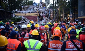 Rescue workers evacuate the place where they were working after a seismic alert sounded in Mexico City on 23 September, four days after the powerful quake that hit central Mexico.