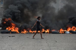 A woman walks past a tyre barricade set ablaze by demonstrators on the fourth day of protests against Haitian president Jovenel Moise and the misuse of Petrocaribe funds arising from an oil deal with Venezuela.