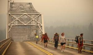 Pedestrians walk off a bridge amid heavy smoke from the Eagle Creek wildfire.