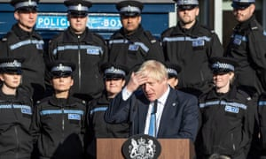Boris Johnson making a speech with police recruits behind him