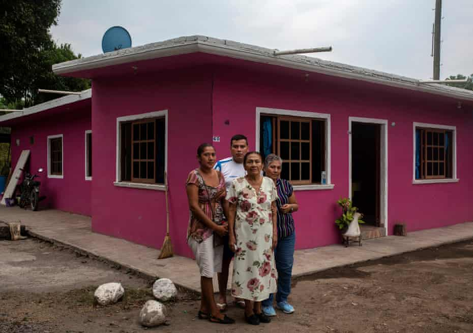 Diogenes Mexicano, (C), mother of Medel, Judit Huesca and Ismael Huesca, sons of Medel,(L), and the sister of Medel, Adelina Huesca, (R), poses in front of the house he built with remittances Medel Huesca, Mexican migrant who died by COVID19 in New York, in the community park of Carretas, Veracruz, Mexico, on May 05, 2020.