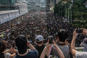 Hong Kong. People take photographs as protesters march on the road below them during a demonstration against the extradition bill