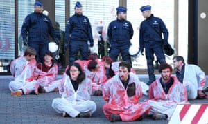 Police stand guard as activists wearing suits covered in fake blood take part in protests against the Comprehensive Economic and Trade Agreement (Ceta) in front of the EU council building in Brussels on 30 October.
