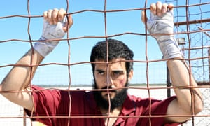 A man behind a wire fence