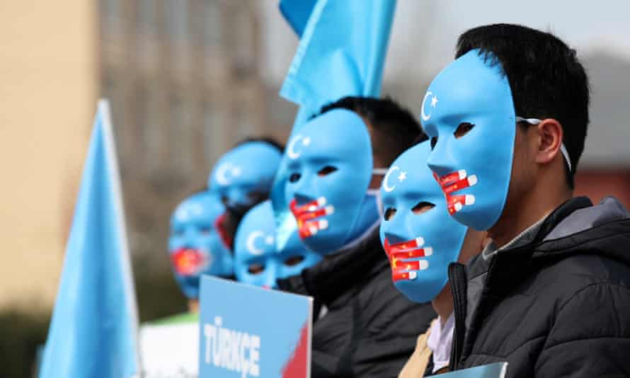 Uighur protesters in Istanbul, Turkey, hold Uighur flags and placards at a protest against China.