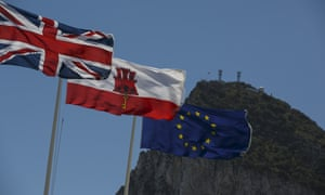 Flags of the United Kingdom, Gibraltar and the European Union are flown while the Gibraltar Rock is seen on the back at the Spain-Gibraltar border