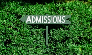 Sign Pointing To Admissions Against A Green Backdropcould be for a school or a museum