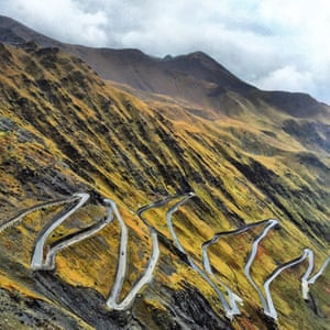 A road twists and curves up the dramatic side of a mountain in the eastern Alps, northern Italy.
