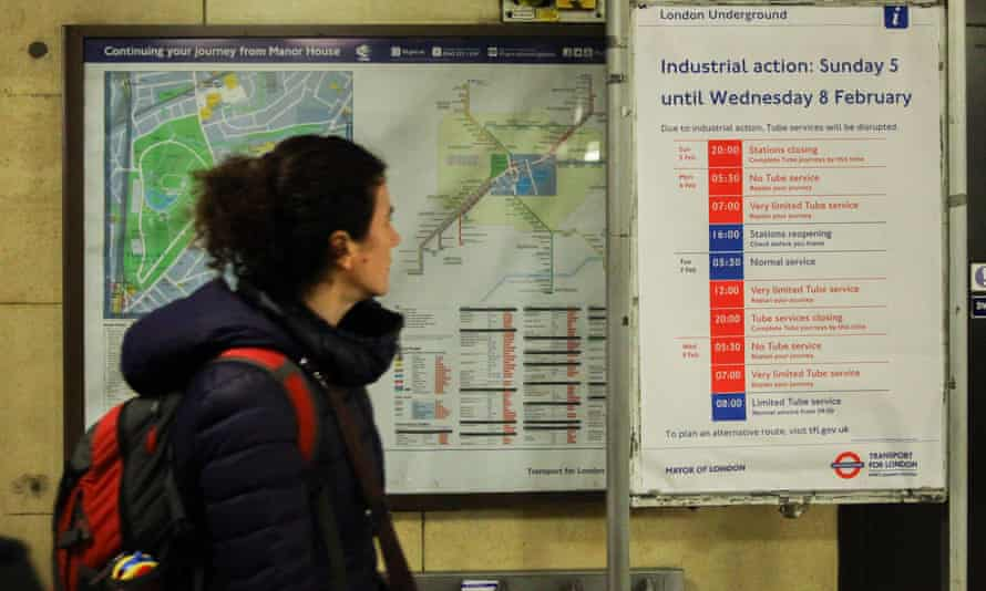 A commuter passes a London Underground tube strike poster at Manor House.