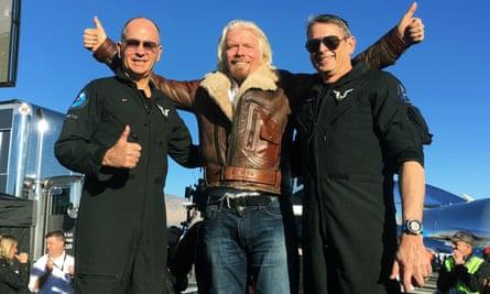 "Richard Branson, center, celebrates with pilots Rick ""CJ"" Sturckow, left, and Mark ""Forger"" Stucky, right"
