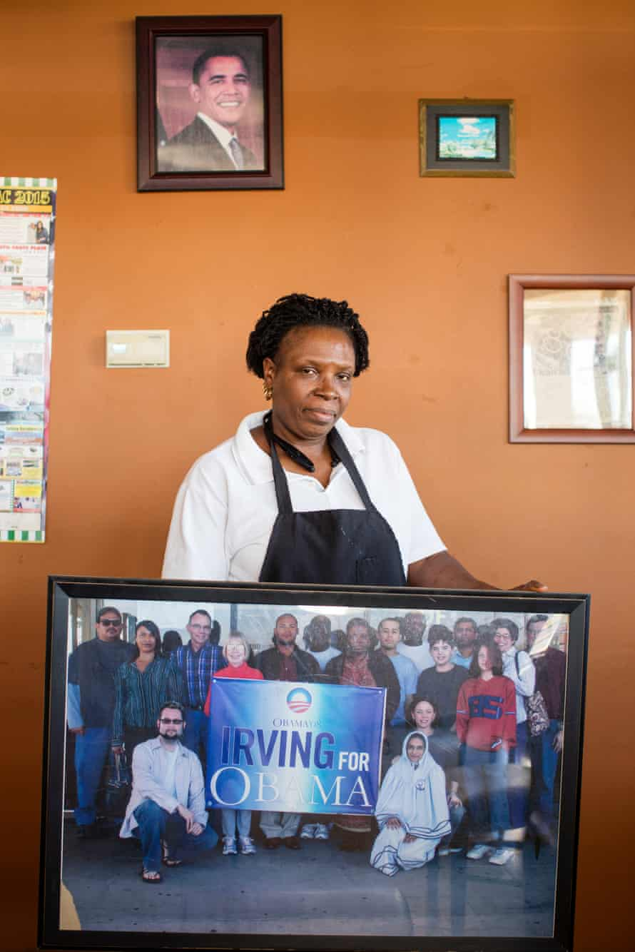 Grace Ndam, owner of the African Village Restaurant holds a photograph showing all the local people that mobilised here in support of Barack Obama during past Presidential elections.