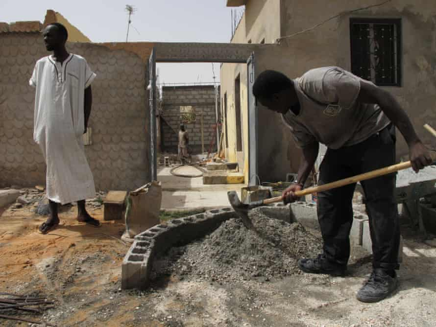 Vieux Fall, left, stands in the family compound in Nouakchott, Mauritania, as builders work