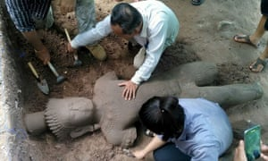 Archaeologists excavate a statue believed to have once stood guard over an ancient hospital at Cambodia's famed Angkor temple complex.