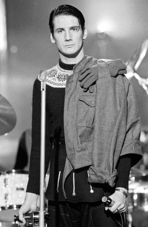 Tony Hadley during the band's debut video shoot, wearing a forest green Alpine jumper and a military flying jacket draped across one shoulder.