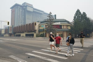 Tourists with their masks on walk outside Harrah's casino on the California-Nevada state line.