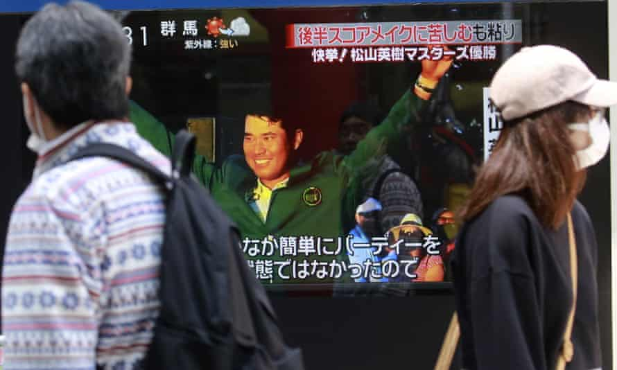 People in Toyko walk past a TV news channel reporting on Matsuyama's victory