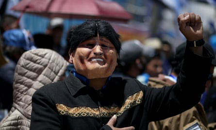 A Mas supporter in an Evo Morales mask  raises a clenched fist