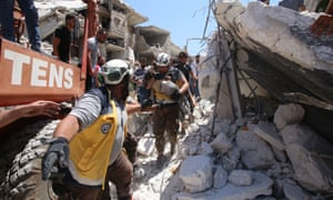 Members of the Syrian civil defence, known as the White Helmets, pull out an injured child from under the rubble after a reported Russian air strike on Maaret al-Numan in Syria's northwestern Idlib province on 22 July 2019