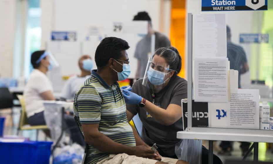 A staff member gives a Covid-19 vaccine to a man at a clinic at Save Max Sports Center in Brampton, Ontario on 10 July.
