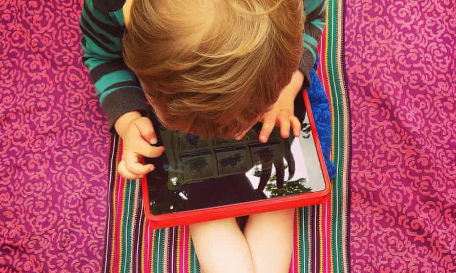 A young boy playing on a tablet.
