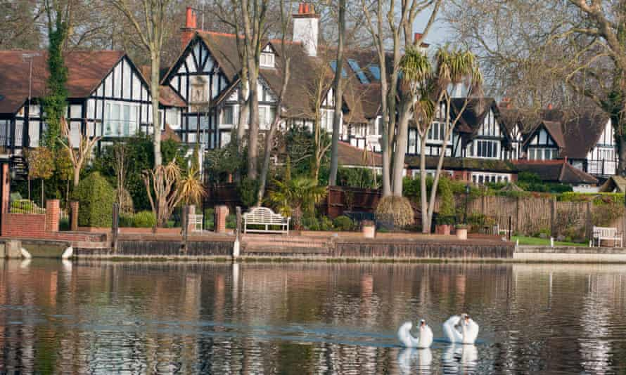 Two mute swans glide in front of upmarket property on the river Thames at Maidenhead