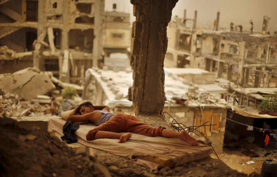 A Palestinian boy sleeps on a mattress inside the remains of his family's house, that witnesses said was destroyed by Israeli shelling during a 50-day war in 2014 summer, during a sandstorm in Gaza September 8, 2015.
