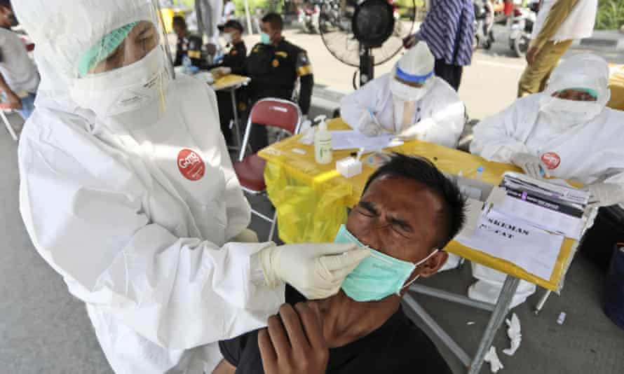 A medical worker collects a nasal swab sample from a man during a mandatory coronavirus test for those traveling between Madura Island and the provincial capital of Surabaya, Indonesia, Monday, 21 June 2021.