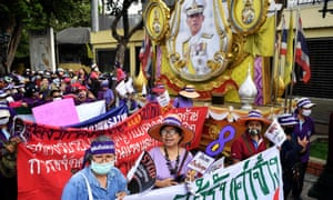 Members of Thai labour rights groups and state enterprise unions walk past a portrait of Thailand's King Maha Vajiralongkorn as they march for labour rights on International Womens Day in Bangkok on March 8, 2020.