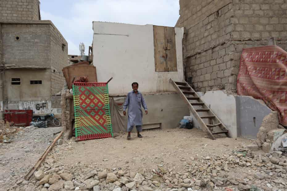 Muhammad Shahid on the rubble where he used to have two rooms that were bulldozed.