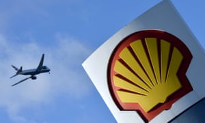 Passenger plane flies over a Shell logo at a petrol station in west London