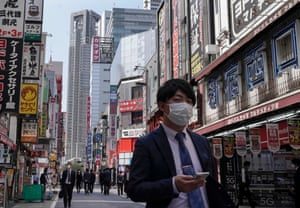 A businessman wearing a protective mask walks at Shinjuku in Tokyo, Japan.