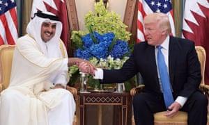 Donald Trump shakes hands with Qatar's Emir Sheikh Tamim Bin Hamad Al-Thani.