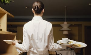 Waitress carrying dirty plates in restaurant