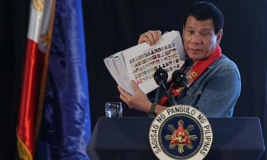 Philippine president Rodrigo Duterte holds a compilation of pictures of people involved in drugs