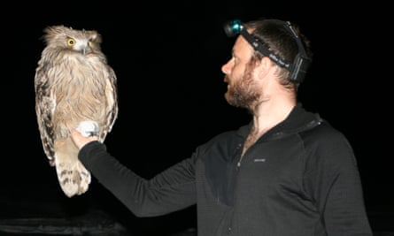 Jonathan Slaght holds a male fish owl in Primorye, Russia, in 2007.