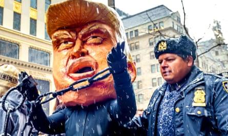 Figure wearing a huge Donald Trump head in a mock arrest in New York