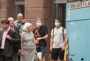 People wait at the lights at Martin Place wearing masks to minimise the exposure to smoke