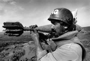 A deminer carefully carries a 120mm mortar to a demolition site in Iraq in 1998