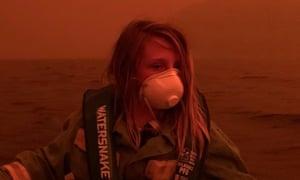 A child sits in a boat offshore from Mallacoota in coastal Victoria as a bushfire raged onshore on New Year's Eve 2019.