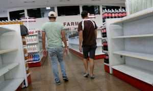 Two men looks for goods in a supermarket amid empty shelves in the Petare district of Caracas on Thursday.