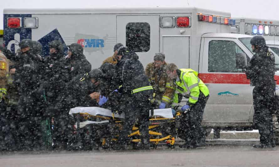 A victim is taken away from the clinic under heavy guard.