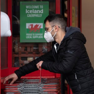 A shopper wearing a face mask takes a basket at an Iceland store in Caerphilly, Wales.
