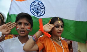 Students salute next to a flag as they sing the national anthem in Hyderabad