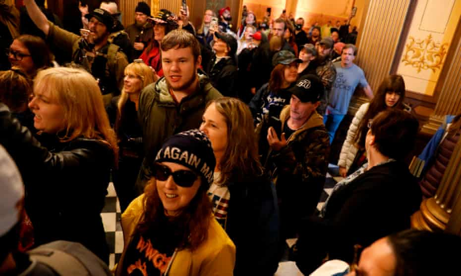 Protesters carrying mobile phones try to enter the Michigan house of representatives chamber during an anti-lockdown protest in Lansing on 30 April.