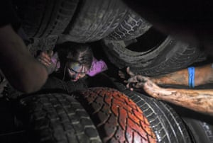 Novosibirsk, RussiaA participant crawls through tyres during the Race of Heroes night obstacle course event