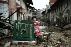A woman sits down in a street damaged by super typhoon Nepartak in Minqing, China