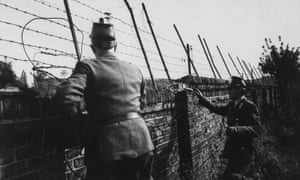 Two West Berlin police peer over the Berlin wall into eastern sector in hopes of helping someone escape to freedom on their side.